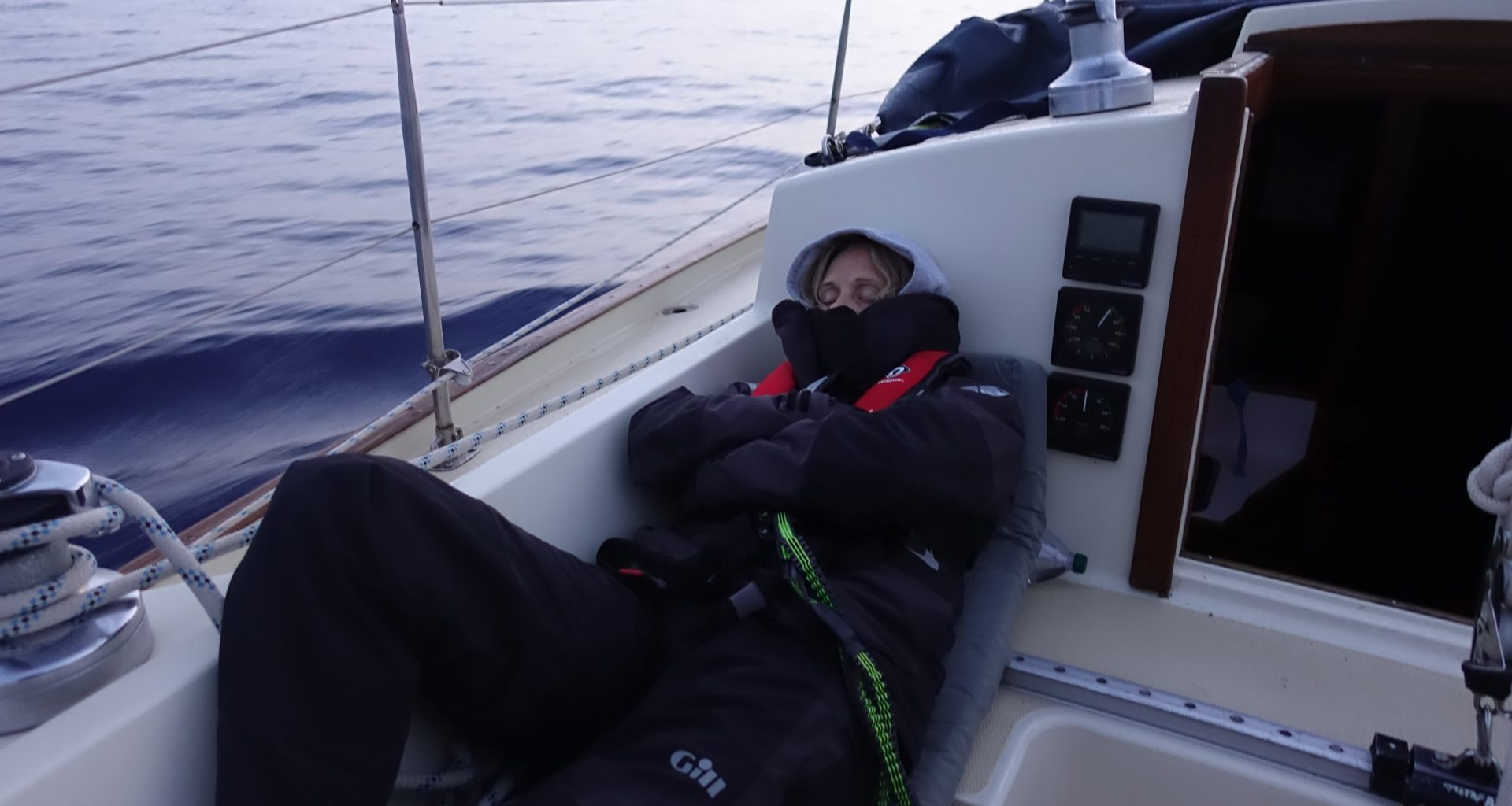 person sleeping in a cockpit of a sailing boat
