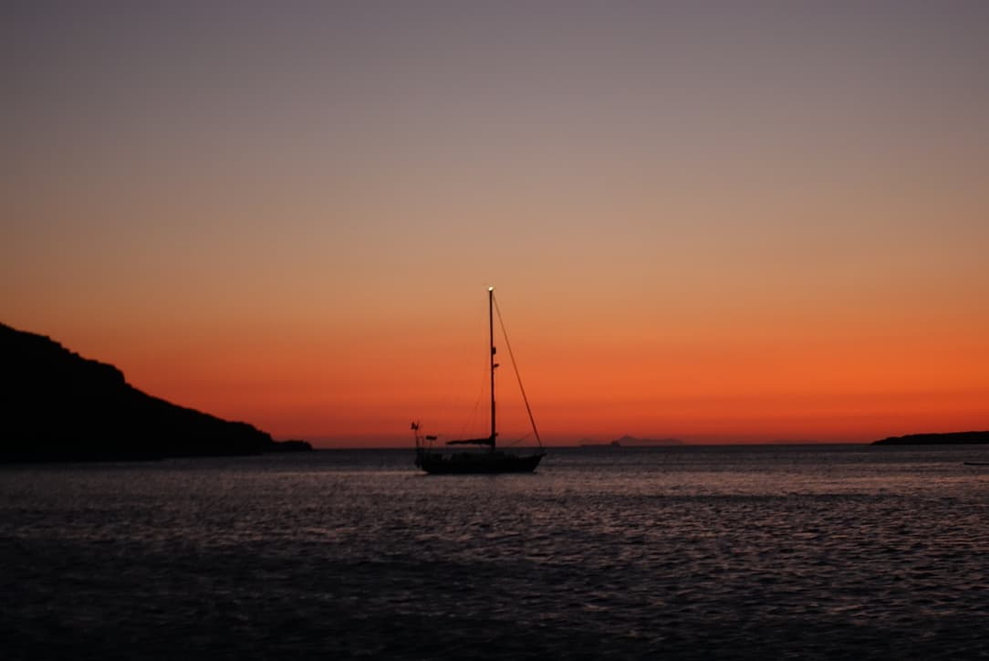 sailing boat anchored in a sunset