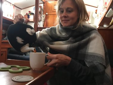 person pouring tea from a teapot on a boat