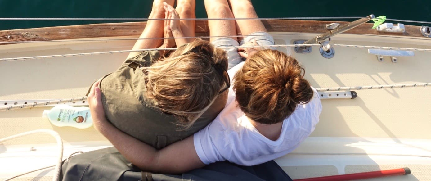 two girls hugging on a sailing boat