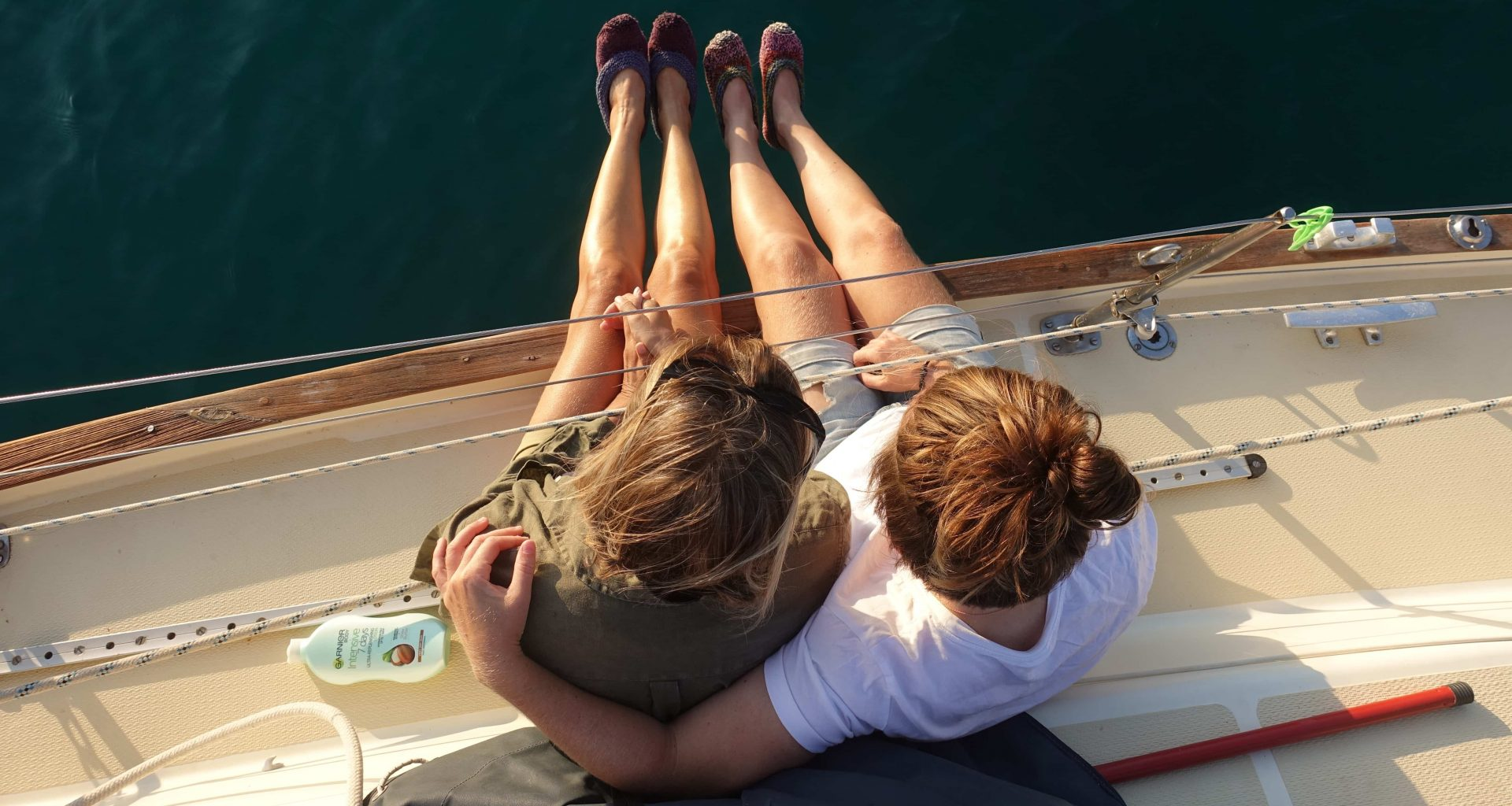two girls having a hug on a sailing boat